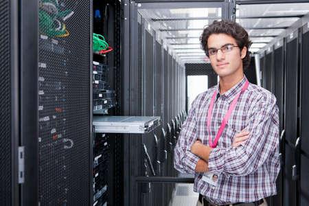 replacing: Technician, looking at camera, replacing server in server cabinet