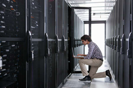 server farm: Technician, kneeling with laptop, checking aisle of server storage cabinets in data center LANG_EVOIMAGES