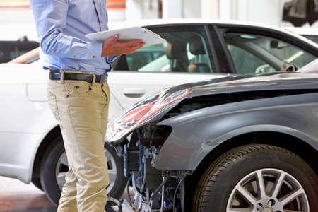 pileup: Insurance assessor inspecting damaged vehicle