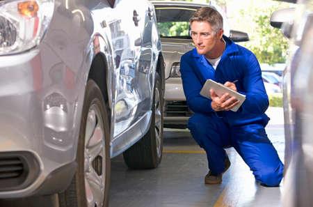 Mechanic inspecting damaged vehicle Stock Photo