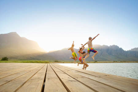 leap: Family, in swimwear, jumping into a lake from a jetty