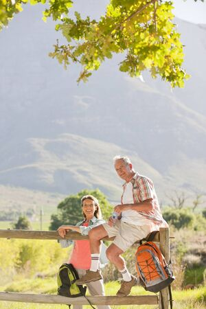 Senior couple resting on a fence in a rural setting