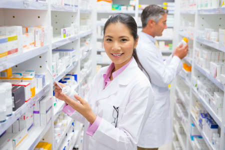 Pharmacist, holding medication pot and prescription, smiling at camera in pharmacy