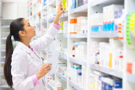 Pharmacist, holding prescription, looking for medication on pharmacy shelf Stock Photo