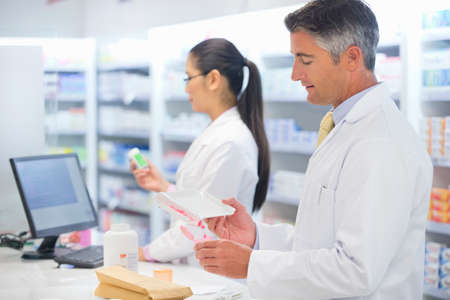 dispensing: Pharmacist counting and dispensing medication behind pharmacy counter