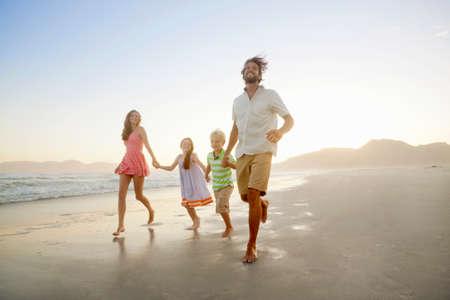 Happy family, holding hands, running on sunny beach