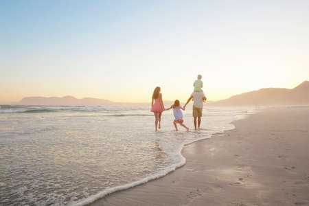 Happy family walking into distance, holding hands and son having piggy-back, on sunny beach LANG_EVOIMAGES