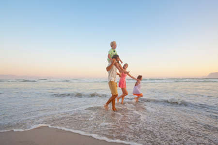 piggyback: Happy family walking through waves, holding hands and son having piggy-back, on sunny beach