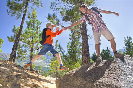 liberated: Father helping son climb, on mountain path