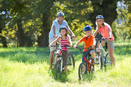 mountain bicycling: Family, mountain biking, in treelined field LANG_EVOIMAGES
