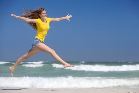 liberated: Happy woman leaping in air on sunny beach LANG_EVOIMAGES