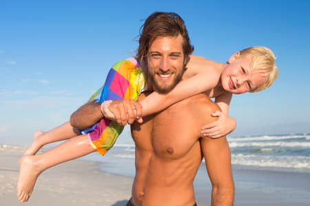 hand lifted: Portrait of father with son on shoulder, smiling at camera, on sunny beach