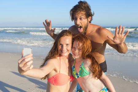 family fitness: Portrait of happy family, taking selfie on sunny beach