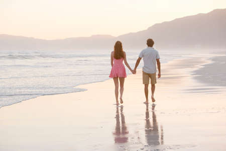 Couple walking into distance, holding hands, on sunny beach