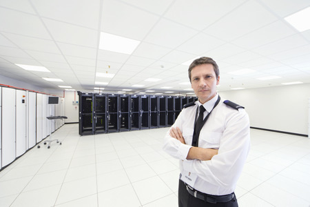 guarding: Security guard standing with arms crossed, looking at camera, in server room