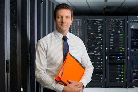 Manager holding folder, looking at camera, in server room