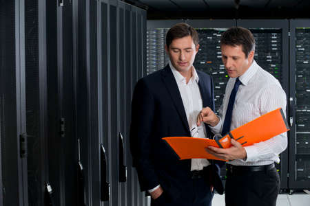 Two managers, looking at folder, in server room Stock Photo