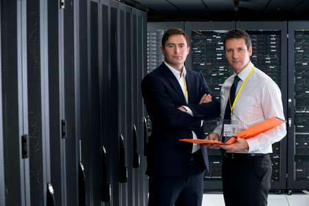 Two managers, looking at camera, in server room Stock Photo