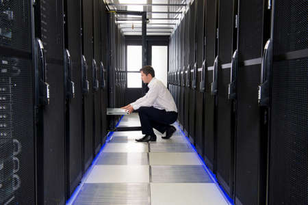 Technician replacing server in server cabinet Stock Photo
