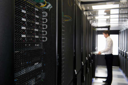 server farm: Technician replacing server in server cabinet LANG_EVOIMAGES