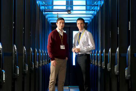 Manager and technician, looking at camera, in aisle of server room Stock Photo