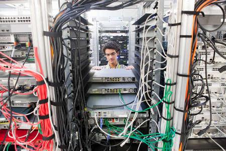 replacing: Technician replacing server in server cabinet LANG_EVOIMAGES