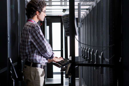 Technician working on computer in aisle of server storage cabinets