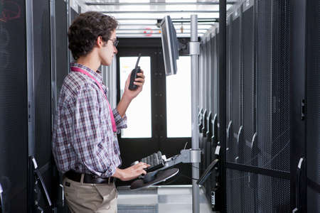 Technician, on walkie talkie, working on computer in aisle of server storage cabinets Stock Photo