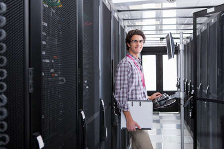 Technician, smiling at camera, working on computer in aisle of server storage cabinets Stock Photo