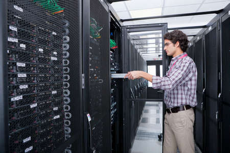 replacing: Technician replacing server in server cabinet LANG_EVOIMAGES