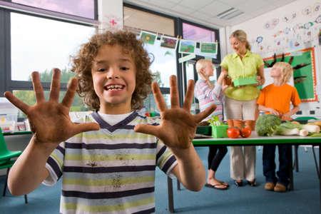 manos sucias: Muchacho sonriente estudio de la biolog�a en el aula mostrando las manos sucias LANG_EVOIMAGES