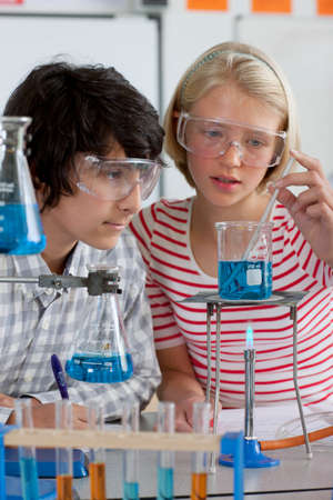 Students performing experiment in school chemistry laboratory LANG_EVOIMAGES