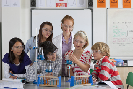 test tube holder: Teacher watching students performing experiment in school chemistry laboratory