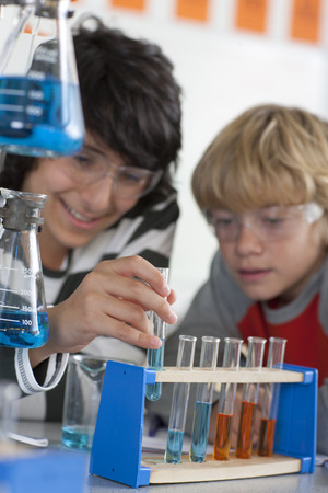 test tube holder: Students performing experiment in school chemistry laboratory LANG_EVOIMAGES