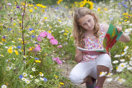 girl squatting: Girl squatting on path looking at botany book in field of wildflowers