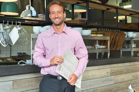 keuken restaurant: Lachend ondernemer houden menu in restaurant LANG_EVOIMAGES