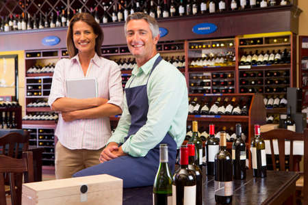 Smiling business owners with digital tablet in wine shop Stock Photo