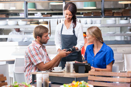 card reader: Customers paying waitress with credit card reader in restaurant