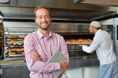 small business owner: Baker holding bread in bakery kitchen with business owner LANG_EVOIMAGES