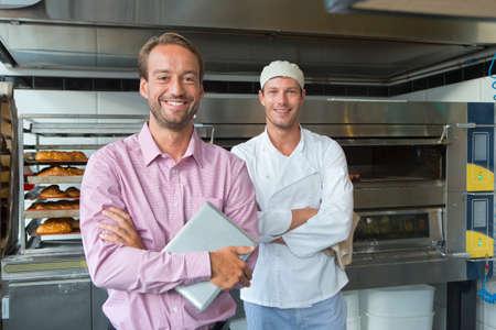 Geschäftsinhaber und Bäcker in der Bäckerei Küche mit digitalen Tablet-