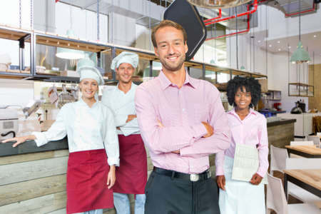 small business team: Business owner with chefs and waitress in restaurant