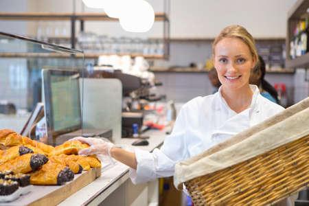 emptying: Smiling baker emptying basket of bread in bakery