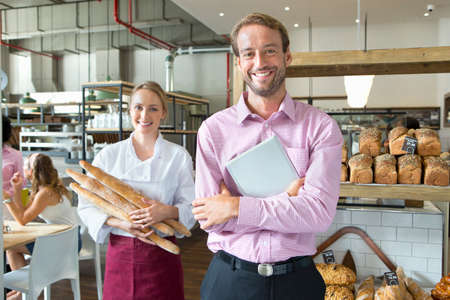 french ethnicity: Smiling baker with business owner holding bread in bakery LANG_EVOIMAGES