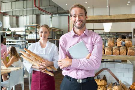 Sourire boulanger avec du pain propriétaire d'affaires tenant en boulangerie LANG_EVOIMAGES