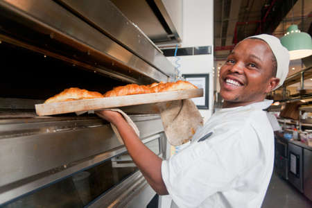 Smiling baker removing tray of bread from oven in bakery