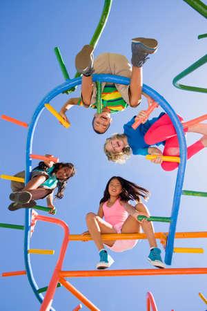 directly below: Children sitting on monkey bars at playground