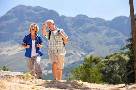 parejas caminando: Mayor Pareja senderismo en la ladera rural LANG_EVOIMAGES