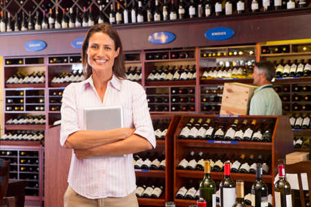 business products: Smiling business owner with digital tablet in wine shop