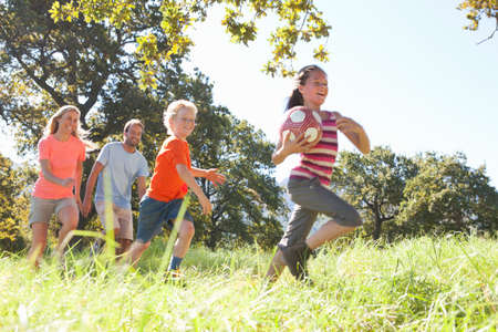 level playing field: Parents and children running with ball in rural field
