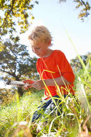 level playing field: Boy examining feather in rural field